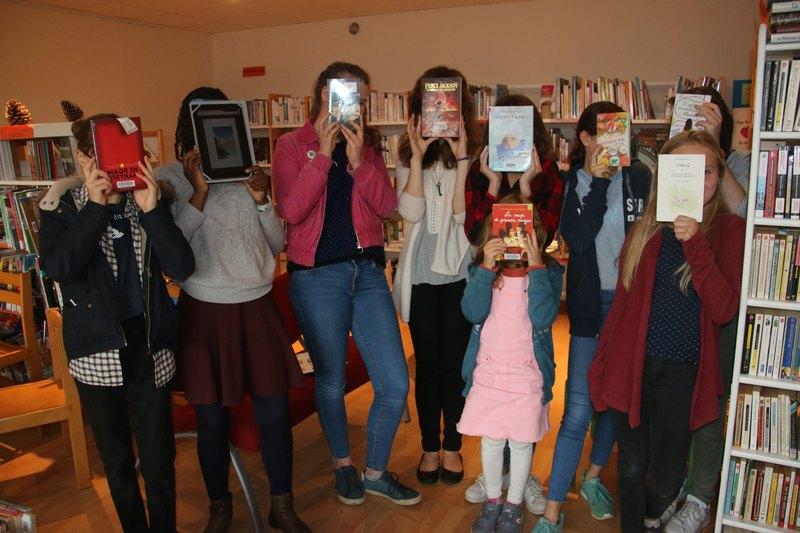 les enfants levant leur livre coup de coeur à hauteur du visage